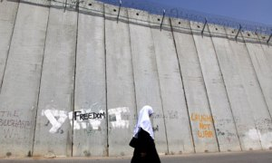 A Palestinian woman walks past the wall on the Israeli side of East Jerusalem.